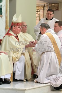 Lance Martin kneels before Bishop Malooly and join hands during his Ordination at the Cathedral of St. Peter, Saturday, May 28, 2016. wwwDonBlakePhotography.com
