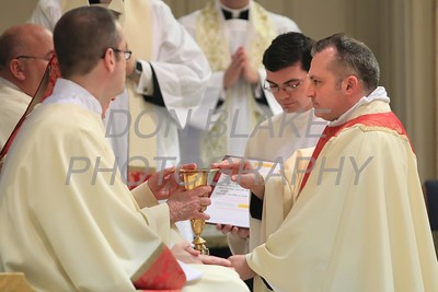 Lance Martin holds the bread and chalice with Bishop Malooly during his Ordination at the Cathedral of St. Peter, Saturday, May 28, 2016. wwwDonBlakePhotography.com