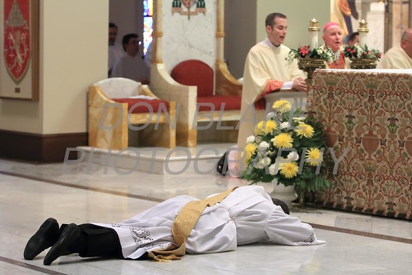 Lance Martin prostrates himself as Bishop Malooly all in attendance pray during his Ordination at the Cathedral of St. Peter, Saturday, May 28, 2016. wwwDonBlakePhotography.com