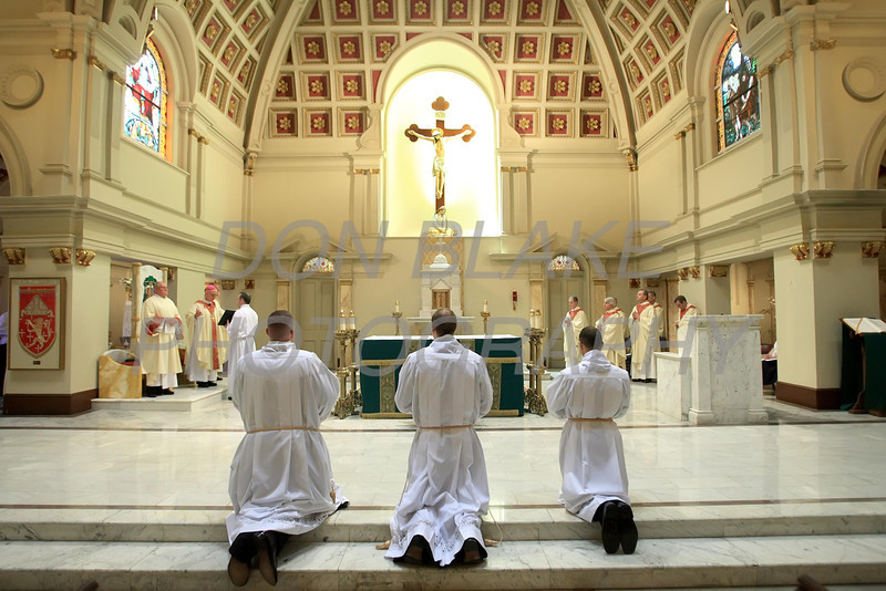 Christopher Coffiey (left). Glenn Evers, and Brian Lewis kneel on the alter during their Ordination to the Transitional Deacons at the Cathedral of St. Peter, Saturday 16, 2012. photo/www.DonBlakePhotography.com
