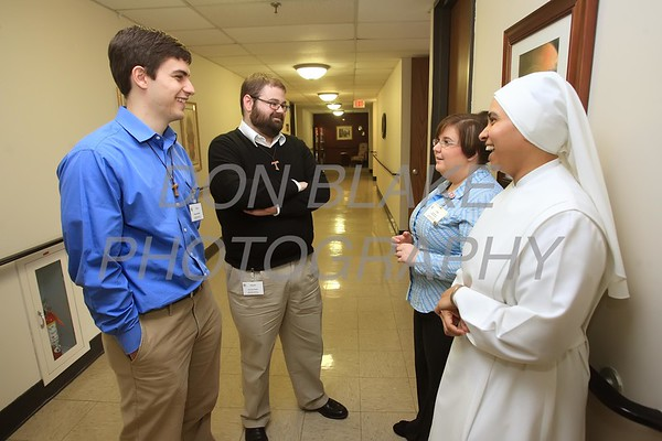 Casey Cole and Dennis Bennett a Franciscan novices talks to Jody Howell and Sr. Georgia George at Little Sisters of the Poor's Jeanne Jugan Residence. Casey and Dennis are Franciscan novice who are volunteering at Jeanne Jugan. photo/ www.DonBlakePhotography.com