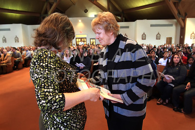 Nada Ann Jones from Holy Family Parish (left) holds the Book of the Elect as Catechumen Debbie Crutchfield signs during the Rite Election at Holy Cross Church, Dover, Del., Saturday, February 25, 2012. photo/ www.DonBlakePhotography.com