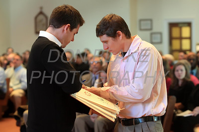 Nick Boggs from St. Anthony of Padua (left) holds the Book of the Elect as Catechumen Jeremy Smith signs during the Rite Election at Holy Cross Church, Dover, Del., Saturday, February 25, 2012. photo/ www.DonBlakePhotography.com
