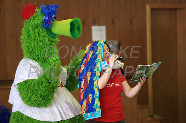 The Phillie Phanatic helps 2nd grade teacher Kate Julian with her towel as she reads the book about him at Our Lady of Fatima School, Friday, March 23, 2012. photo/ www.DonBlakePhotography.com