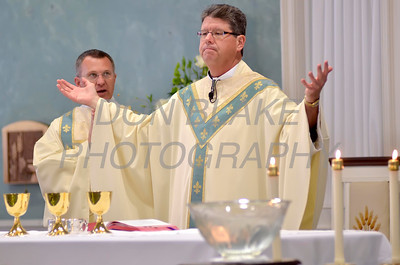 Fr. Paul Campbell blesses the host during the First Communion Mass at Sacred Heart Church, Chestertown, Maryland, Sunday. May 6, 2012. photo/ www.DonBlakePhotography.com