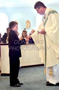 Jacob Pratt receives his first Communion from Fr. Paul Campbell during First Communion Mass at Sacred Heart Church, Chestertown, Maryland, Sunday. May 6, 2012. photo/ www.DonBlakePhotography.com