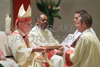 Bishop Maooly hands the Book of Gospels to Richard Jasper during his Ordination to the Diaconate at St. Elizabeth Church, Sunday, May 22, 2016. wwwDonBlakePhotography.com