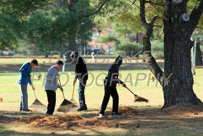 St. Elizabeth High School Sophomores rake pine seedles as they work on a service project beautifying All Saints Cemetery, Thursday, Octeber 24, 2013. wwwDonBlakePhotography.com