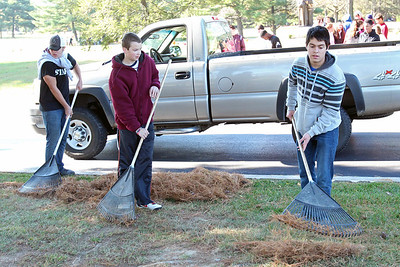 St. Elizabeth High School Sophomores Connor Davis (left), Colin Backer, and Santi Marin rake pine seedles as they work on a service project beautifying All Saints Cemetery, Thursday, Octeber 24, 2013. wwwDonBlakePhotography.com