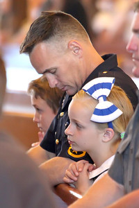 Crop. Thomas Donlon from the New Castle City Police Department prays with kids Josh age 11 and Madilyn age 9 who attend St. John the Beloved School during the annual Blue Mass at St. John the Beloved Church, Friday, May 3, 2013. photo/ www.DonBlakePhotography.com