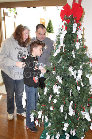 Phil Grimes his wife Theresa and his son Jeremy take a request off the Angel Tree during St. Helena's Christmas Bazzar, Saturday, November 9, 2013. photo/www.DonBlakePhotography.com