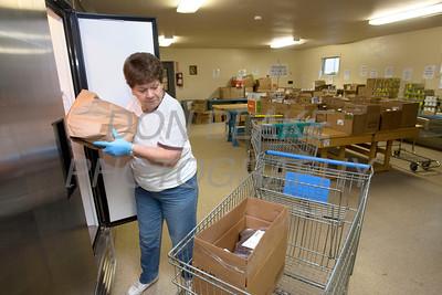 Carolyn Swain loads food into a clients cart St. Martin's Barn. photo/Don Blake Photography.com