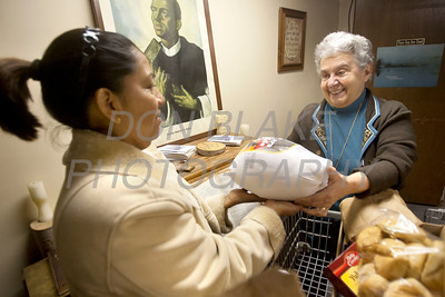 St. Patricia Gamgort who help start St. Martin's Barn 29 years ago (right) hands client Maricela Lopez-Cancino her turkey at St. Martin's Barn. photo/Don Blake Photography.com