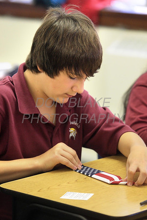 """7th grader Sam Oldham folds a pocket flag as the seventh grade Social Studies class at St. Elizabeth School work with ladies from the American Legion on a """"Pocket Flag Project"""". There was a brief presentation Êthen students folded pocket flags for members of our military which will include messages from the students. These flags will then be distributed to military personnel to carry in their pockets as a reminder of our gratitude for their service. photo/Don Blake Photography.com"""