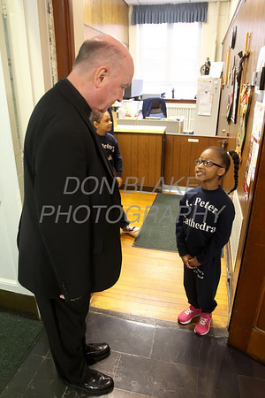Bishop Malooly is greeted by 3rd grader Aniyah Springer as he enters in office at the Cathedral of St. Peter School for his annual visit Thursday, October 10, 2013. wwwDonBlakePhotography.com