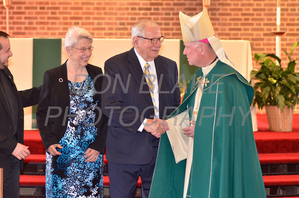 Bishop Malooly shakes hands with award recipients Mr. & Mrs. Raymond Sarlitto of St. Mary Star of the Sea/Holy Savior Parish during the Medal of Merit award ceremony at St. John the Beloved, Sunday, October 21, 2012. www.DonBlakePhotography.com
