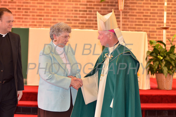 Bishop Malooly shakes hands with award recipient Rosanne Christopher of St. Thomas the Apostle Parish during the Medal of Merit award ceremony at St. John the Beloved, Sunday, October 21, 2012. www.DonBlakePhotography.com