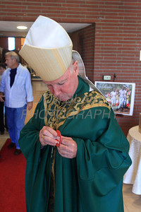 Bishop Malooly puts on his Dialog Here! button before handing out copies of The Dialog Newspaper after mass at St. Mary of the Assumption Parish Church, Sunday, October 16, 2011. The Dialog/Don Blake