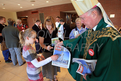 Bishop Malooly hands 9 year old Katelyn Folmer and her mother Beverly Folmer a copy of The Dialog Newspaper after mass at St. Mary of the Assumption Parish Church, Sunday, October 16, 2011. The Dialog/Don Blake