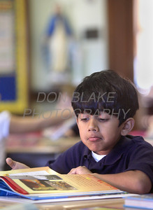 Amogh Baradwaj looks over his new school books in Mrs. Rombach 2nd grade class during the first day of school at All Saints Catholic School, Elsmere, Del., Tuesday, August 30, 2011. The Dialog/Don Blake