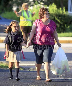 Antoinette Fontana walks her daughter 3rd grader Madelyn Fontana a former student from St. Matthew School across the parking lot during the first day of school at All Saints Catholic School, Tuesday, August 30, 2011. The Dialog/Don Blake