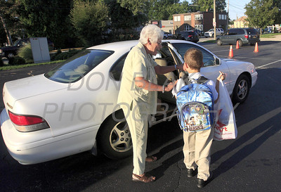 Joan Angiullo helps a student at drop off during the first day of school at All Saints Catholic School, Tuesday, August 30, 2011. The Dialog/Don Blake