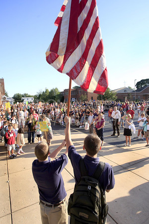 The entire student body recite the pledge allegiance as the flag is held high before entering school during the first day of school at All Saints Catholic School, Tuesday, August 30, 2011. The Dialog/Don Blake