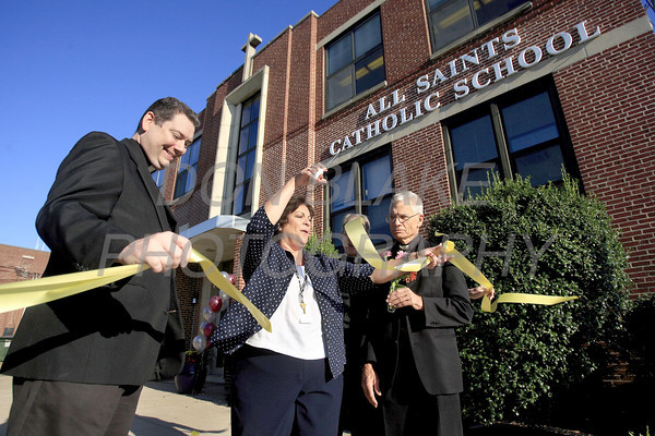 Fr. Timothy Nolan, Principal, Diana Thompson, Fr. John Hynes, and Fr. Charles Dillingham (not shown) cut the ribbon during the first day of school at All Saints Catholic School, Tuesday, August 30, 2011. The Dialog/Don Blake