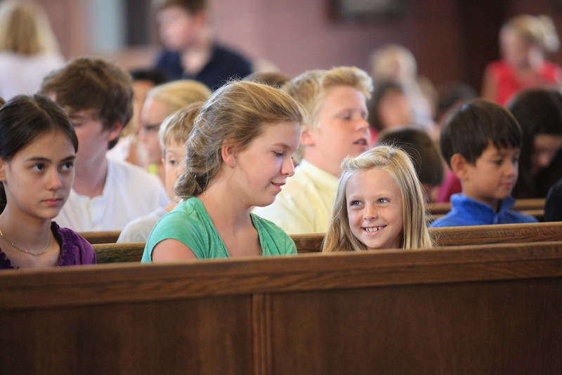 Seventh grader Elyse Lamey talks with her prayer buddy 2nd grader Madison Hazewski before mass during summer religious education class prep at St. Mary of the Assumption, Wednesday, August 15, 2012. photo/www.DonBlakePhotography.com