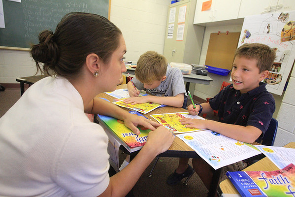 Second teacher Caitlin Gibbons helps 2nd grader Patrick DiDonato with his work sheet during summer religious education class prep at St. Mary of the Assumption, Wednesday, August 15, 2012. photo/www.DonBlakePhotography.com
