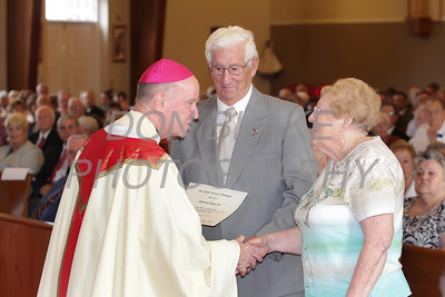 Charles and Marian Otis who have been married for 65 years shake hands with Bishop Malooly during the annual Wedding Anniversary Mass at St. John the Beloved Church, September 15, 2013. wwwDonBlakePhotography.com