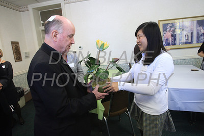 Bishop Malooly receives a plant from Arial Wang 11th grade one of the foreign students that is attending St. Mark's High School during a lunch with all the foreign students, Monday, September 24, 2012. photo/www.DonBlakePhotography.com