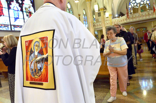 Bishop Malooly distributes Holy Communion wearing a chasuble depicting Our Mother of Sorrows in remembrance of the victims of the terrorist attacks during a 9/11 10th anniversary mass at St. Hedwig Church, Sunday, September 11, 2011. The Dialog/Don Blake