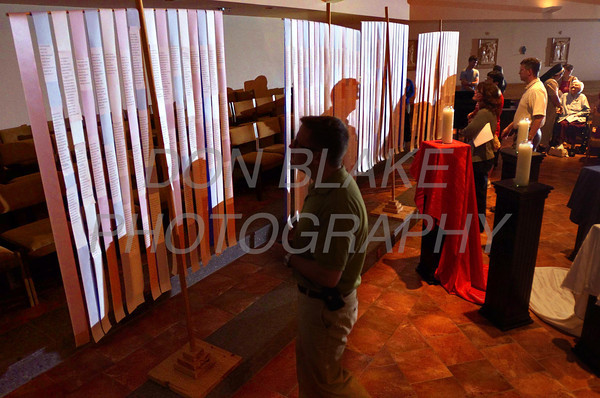 People read the names on the 4 banners with the names of victims of the terrorist attacks during a 9/11 10th anniversary candlelight Vespers at Holy Angels Church, Sunday, September 11, 2011. The Dialog/Don Blake