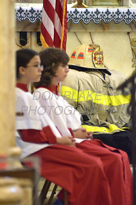 Alter servers Eddie Goralski age 11 and Savanna Jones age 11 sit on the alter next to a fireman's jacket and helmet during a 9/11 10th anniversary mass at St. Hedwig Church, Sunday, September 11, 2011. The Dialog/Don Blake
