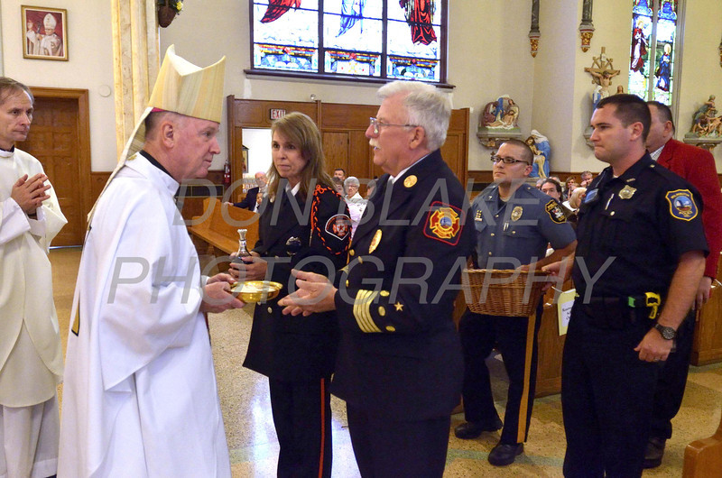 Bishop Malooly receives the gift from Eve M. Wojcieshowski from 5 Points Fire Company, Deputy Chief Allen Huelsenbeck from the Wilmington Fire Department, John Mitchell from the Elsmere Police Department, and Rob Steele from the Wilmington Police department during a 9/11 10th anniversary mass at St. Hedwig Church, Sunday, September 11, 2011. The Dialog/Don Blake