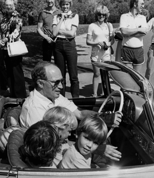 Prime Minister Pierre Trudeau and his three sons, Justin, 9, with his back to the camera, Michel, 5, watching the camera, and Sacha, 7, watching his father's hand, prepare for a drive to the prime minister's cottage at Harrington Lake, Qc., Sept. 6, 1980. (CP PHOTO/Fred Chartrand)