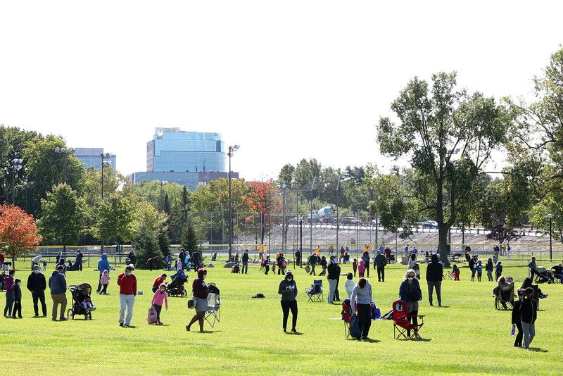 Hundreds of people and family members line up around a football field for COVID-19 testing at Brewer Park in Ottawa.