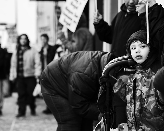 A young man regards protestors from the sidelines.  The protest was in response to Donald Trump's recent declaration of a national emergency at the southern border.  Minneapolis, Minnesota - February 16.