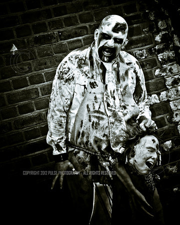 A Zombie butcher holding the head of a surprised person at the gathering point near the West Pier in Brighton.