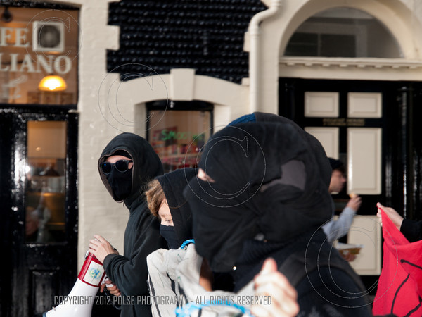 Three hooded and masked demonstrators in Church Street Brighton.