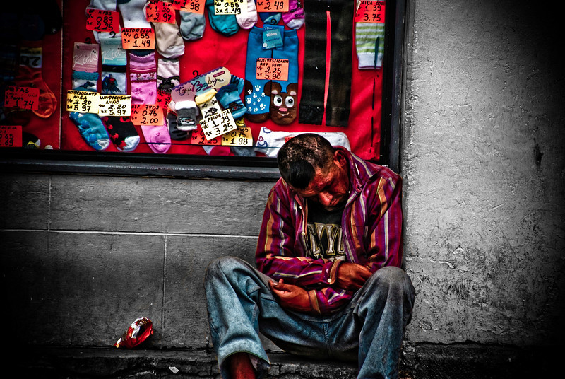 "A homeless man sitting on the curbside appears to be in agony - Quito, Ecuador.  Travel photo from Quito, Ecuador. <a href=""http://nomadicsamuel.com"">http://nomadicsamuel.com</a>"