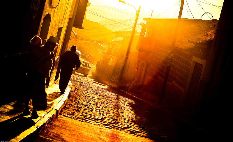 Today's daily travel photo is of a street scene rendered mostly as a silhouette with golden rays of light during sunset in Potosi, Bolivia.