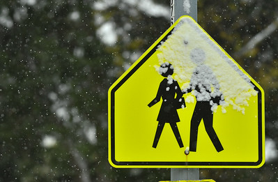 Snow falls on a school crossing sign in Kansas City on Oct. 26, 2020. Photo by Carlos Moreno