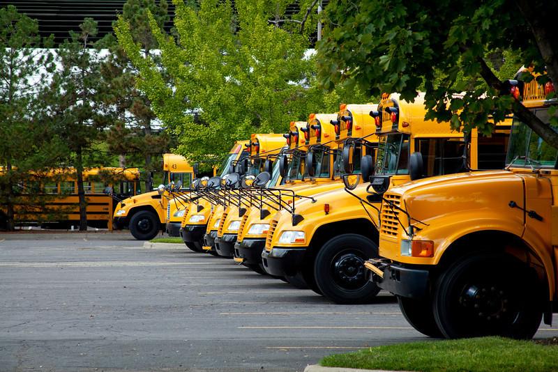 Many orange school busses in a row.