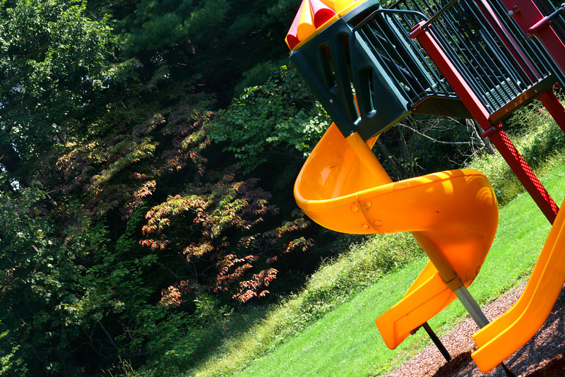 Bright playground equipment against a wooded vista.