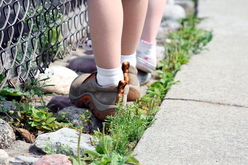 Children walk along a chain link fence.