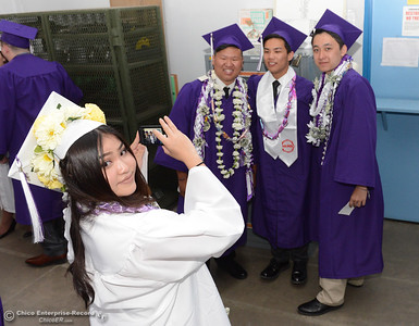 Jasmine Yang gets ready to snap a photo of, left to right, Moua Lee, Wilson Xiong and Devan Lee as the boys pose before Oroville High School's Class of 2016 graduates Friday, June 10, 2016, at Harrison Stadium in Oroville, California. (Dan Reidel -- Mercury-Register)