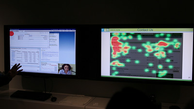 Eye-tracking station. The left screen records where the user's eyes are focusing on the page. The right screen shows a summary hot map indicating the most viewed areas of the page. Red has the highest views.