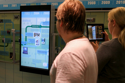Users slide the video screen down a track to interact with the wall sized timeline.